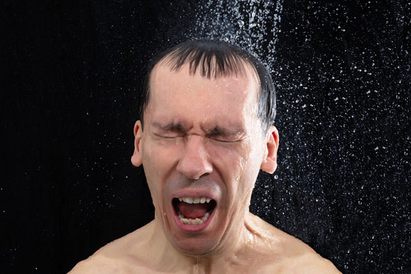 image of a man taking a cold shower due to broken water heater